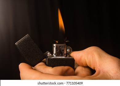 The male hands are setting fire up in zippo for smoking on black background.