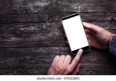 Male hands in shirt touching white smartphone screen on dark rustic wood with copy space. Above view flat lay