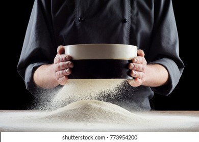 Male hands sifting flour from old sieve on old wooden kitchen table. Isolated on black background.