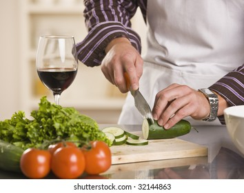 Male hands slicing cucumber on a cutting board. torso and hand shot. square.