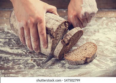 Male hands slicing home-made bread