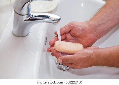 Male hands with soap under running water in the bathroom