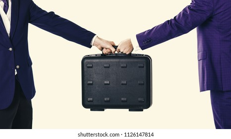 Male hands in suits hold black briefcase. Business exchange concept. Handover of case in hands of business partners, isolated on white background. Male hands carry briefcase for exchange.