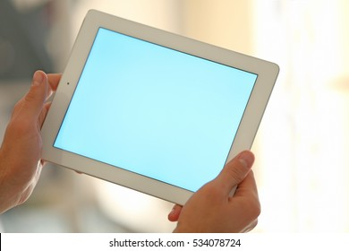 Male hands with tablet on blurred background