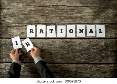 Male hands taking away letters IR from the word Irrational changing it into rational spelled on white cards over rustic textured wooden planks. Conceptual of being objective in decision making.