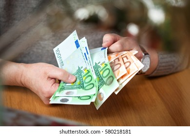 male hands think Euro banknotes. Euro banknotes in denomination of 100 and 50 Euro. Wealthy businessma. Calculate the profit.