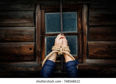 Male hands tied with a rope.