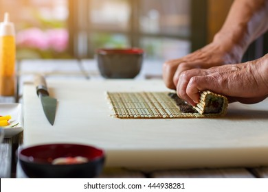 Male hands touching bamboo mat. Small bamboo mat and knife. Experienced sushi chef. Preparing healthy meal with seafood.