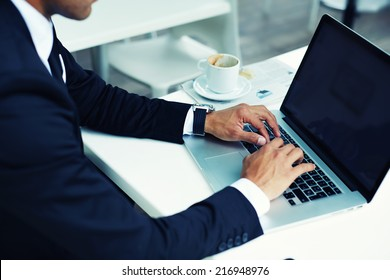 Male hands typing on laptop computer keyboard, businessman seated in cafe working with computer, businesspeople using modern devises, crop of rich businessman in suit working with laptop computer