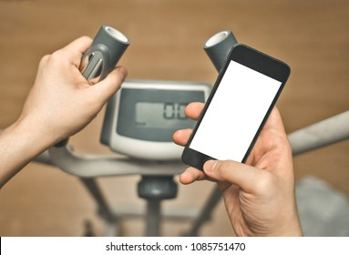 male hands use smart phone with blank touch screen, fitness training on elipsoid, POV