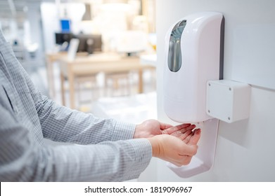 Male hands using automatic alcohol dispenser for cleaning hand in office. Infection prevention concept. Save and clean in public building.
