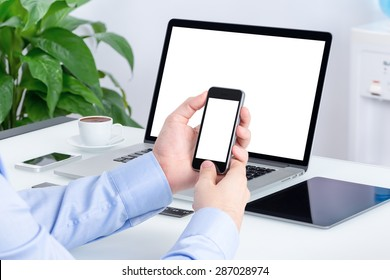 Male hands using smartphone mockup with blank screen at the office desk with an open laptop mockup and tablet computer. All devices in full focus. For responsive design presentation.