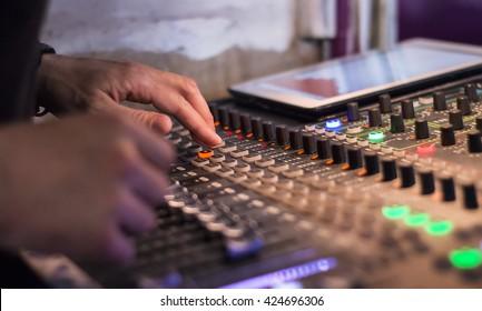 Male hands using a sound digital mixer at a concert
