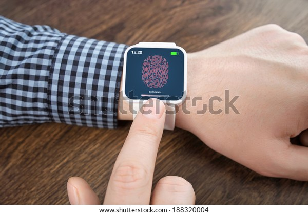 male hands with white smartwatch with a fingerprint on the screen over a wooden table