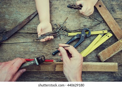 Male hands working on carpenter's desk and working tools.
