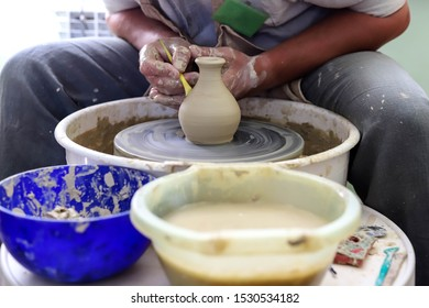 Male hands working on a potter wheel closeup. Making dishes from clay.