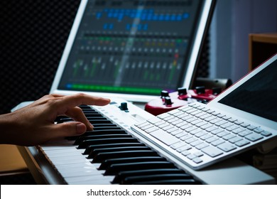 male hands working on sound studio equipments for music production, composing & arranging concept