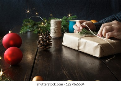 Male hands wrapping gift box on wooden table. Rustic Christmas background. Wrapping presents background