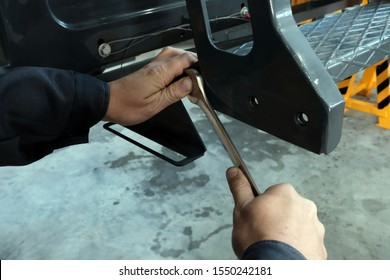Male hands with a wrench. Close-up. A technician at a machine service plant tightens a bolt or nut.