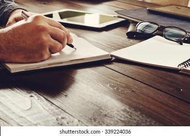 Male hands writing in a notebook on the office table closeup . Free space for text. Copy space.