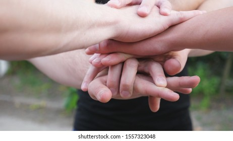 Male hands of young athletes stacking together one by one in unity outdoor. Group of best friends putting their arms in centre of a circle as symbol of friendship and teamwork. Close up Slow motion.