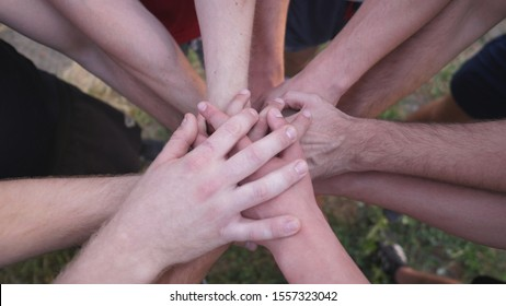 Male hands of young sportsmen stacking together one by one in unity. Group of the best friends putting their arms in centre of a circle and lower them down. Concept of friendship and teamwork.