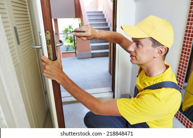 Male handyman carpenter worker at interior wood door lock installation or repairing