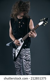 Male hard rock electric guitar musician with long hair. Studio shot against grey.
