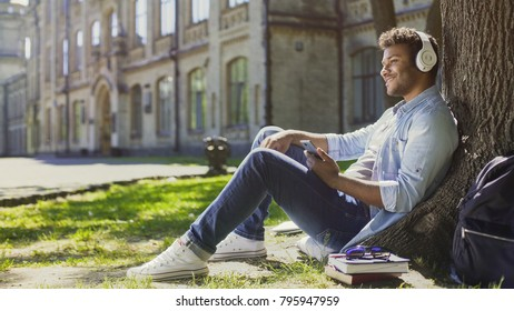 Male in headphones sitting on grass under tree, listening to music, daydreaming