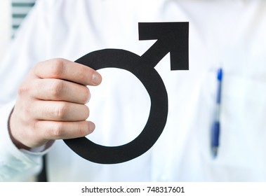 Male health concept. Doctor holding man symbol. Specialist or urologist.