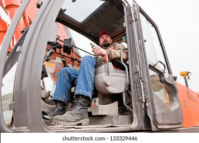 A male heavy equipment operator sitting in the cab of a track-hoe at a construction site on a cloudy winter day.