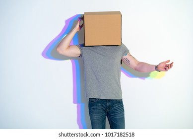 Male hiding face inside pasteboard box. He keeping it by hand. Entertainment concept