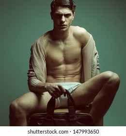 Male high fashion concept. Portrait of a handsome male model sitting on a wooden cube in trendy cardigan & underwear, holding leather bag. Perfect skin & haircut. Vogue style. Copy-space. Studio shot