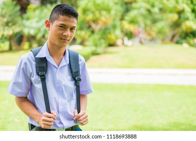 Male high school student is standing on the lawn and wait for going back home, Thailand, southeast Asia.