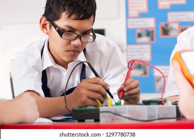 Male high school students studying electronics in class