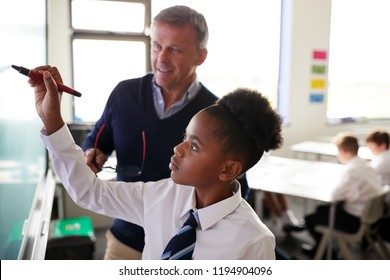 Male High School Teacher With Female Student Wearing Uniform Using Interactive Whiteboard During Lesson