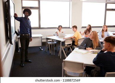 Male High School Teacher Standing Next To Interactive Whiteboard And Teaching Lesson