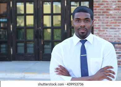 Male High School Teacher Standing By Entrance