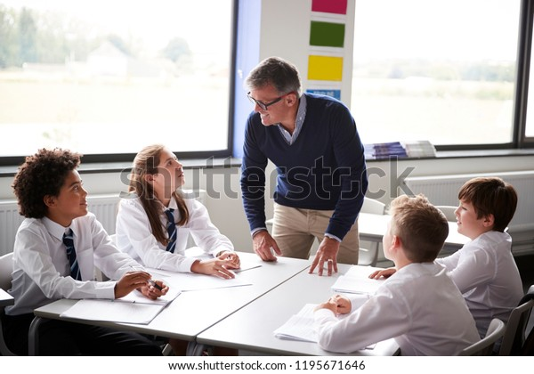 Male High School Tutor Standing By Table With Students Teaching Lesson