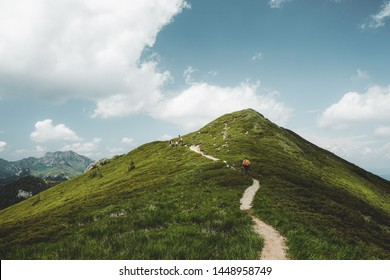 Male hiker with backpack and poles hiking in the Ciucas Mountains in Romania on a sunny day of summer