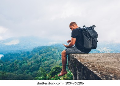 Male hiker with backpack sitting on top with beautiful scenery on Asia environment with green vegetation and high mountains while using good online internet connection in roaming on digital touch pad