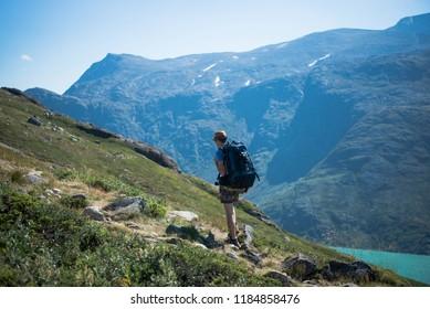 male hiker with backpack walking on Besseggen ridge over Gjende lake in Jotunheimen National Park, Norway