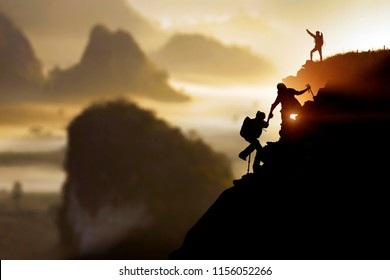 Male hiker celebrating success on top of a mountain in a majestic sunrise and young couple climber helping to hike up . Concept for success ,help,teamwork and Leadership concept .