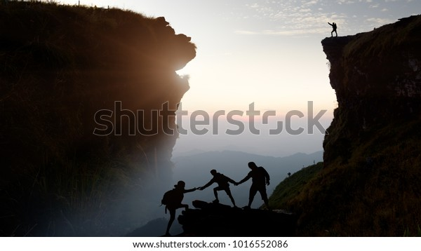 Male hiker celebrating success on top of a mountain in a majestic sunrise and Climbing group friends helping hike up .Teamwork , Helps ,Success, winner and Leadership concept .