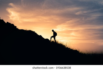 Male hiker climbing up the edge of mountain. Adventure and freedom concept.