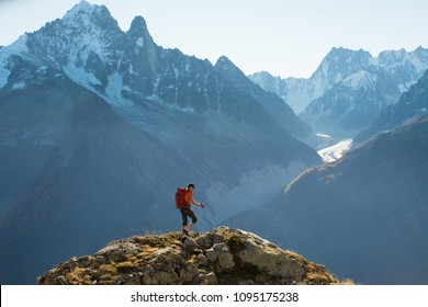 A male hiker climbing to the top of a hill in the high mountains