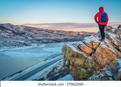 male hiker contemplating winter sunrise over frozen Horsetooth Reservoir  at Rocky Mountains foothills near Fort Collins, Colorado
