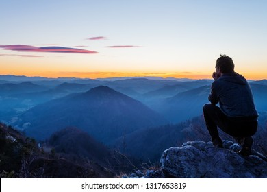 Male hiker crouching on top of the hill and enjoying scenic view of twilight landscape below. Hiking, achievement, expectation, optimism and self-reflection concepts. - Shutterstock ID 1317653819