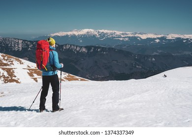 Male hiker hiking with backpack admiring the view of Bucegi mountains in winter / early spring in Romania, Iezer-Papusa mountains