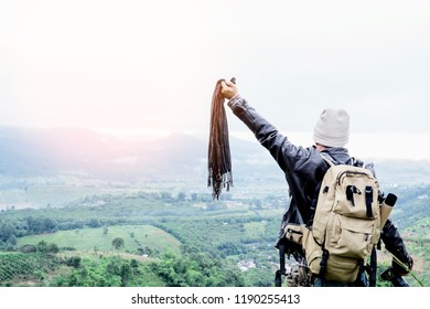 male hiker holding camer and cloth with raised hands